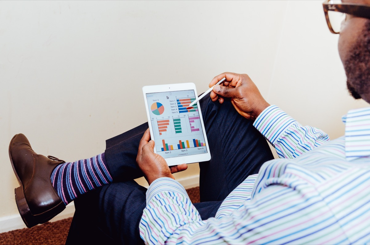 business man using a tablet with charts representing social media ads kpis and metrics