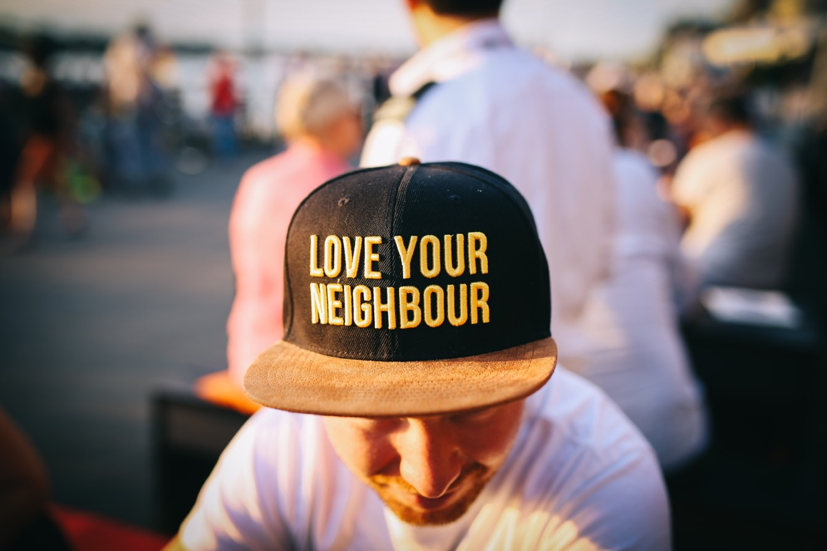 man wearing hat that says: love your neighbor; representing the importance of a localized web presence